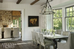 """I chose a soft warm white (Benjamin Moore Titanium) to show off the beams, windows, paneling and floors,"" says Rhodes, who wanted the architectural details to shine. A pair of dining areas, both inside and on a screened porch, each seats 10 people. ""The adults can be on the porch while the kids are inside,"" says Rhodes."