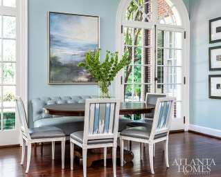 Covered in tufted faux leather from Pindler, the breakfast banquette is as durable as it is attractive. The striped fabric on the side chairs is by Duralee.