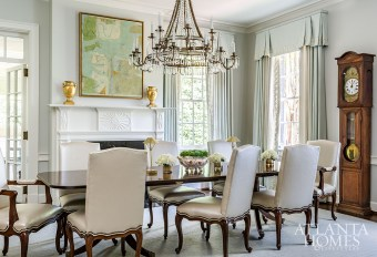 A chandelier by David Iatesta through Ainsworth-Noah softly illuminates a twin pedestal dining table and Louis XV chairs in the formal dining room. The mixed-media painting is by Paul Brigham through Anne Irwin Fine Art.