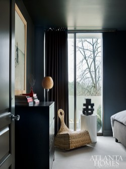 In the second bedroom, the wall color and fabrics exhibit a bronzy hue creating a dark, cozy hideaway.
