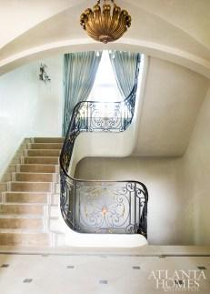 Lueders stone floors, Venetian plaster walls and an iron railing evoke a Parisian sensibility in the main stairway.