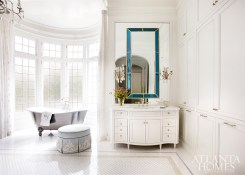 Blue glass mirrors from Dennis & Leen carry the wife's favorite color into the spacious master bathroom, where a soaker tub from Waterworks affords views of the verdant landscaping.