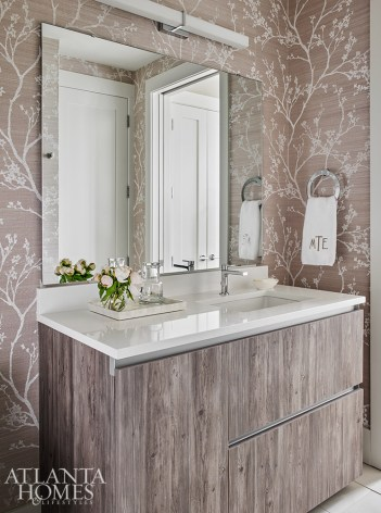 A bold wallcovering by Schumacher juxtaposes the more rustic wooden cabinetry by Pedini in the guest bathroom.