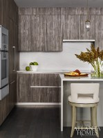 Clad with a waterfall-style Cambria quartz countertop, a lacquered gray island juxtaposes the more rustic wooden kitchen cabinetry, both by Pedini.
