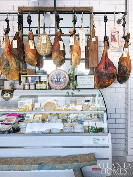 A rack of dry-cured meats accompanies a fridge full of specialty cheeses in the front entrance, offering endless pairings for at-home charcuterie.