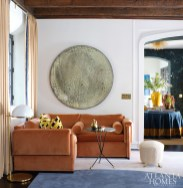 Colorful patterned accent pillows in a Jim Thompson fabric pop against the velvet sectional sofa by Douglass Workroom. The brass floor lamp is by Circa Lighting.