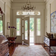 In character of the Greek Revival movement, a sense of formality was applied to the leaded-glass front door and the finely detailed moldings in the entry hall. An antique fixture from Adairsville-based lighting specialist Eloise Pickard provides illumination during the evening. The wood floors are through Vintage Lumber Sales.