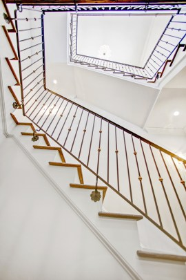 A dramatic, bespoke staircase featuring imported Italian brass detailing.