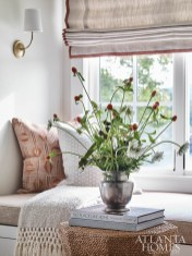 A window seat provides a quiet corner for the daughter to escape. The burnt orange pillow is upholstered in Lee Jofa fabric.