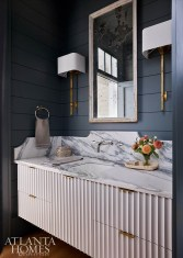 In the powder room, Benjamin Moore's Quarry Rock on the walls contrasts with an antique mirror and honed marble countertops with green veining.