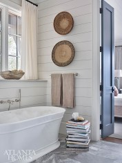 The primary bathroom is on a central axis with the bedroom and looks out onto the balcony. Woven baskets from Lush Life hang above the bathtub.