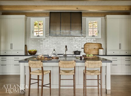 Reclaimed wooden beams and white subway tile provide a layered look in the cream-hued kitchen, while black granite countertops with a leathered finish are both stylish and durable. The custom hood, crafted by a local blacksmith, is the centerpiece of the space.