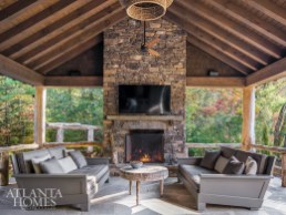 Nearly the size of a twin bed and even more comfortable, a pair of custom sofas face each other in front of the tall stone fireplace on the covered porch off the kitchen. The raffia chandelier is by Masterpiece Lighting.