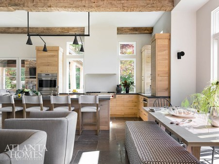 Plaster walls and an integrated hood play off the natural white oak cabinetry built by Otis & Company in the light-filled kitchen and breakfast area. The custom black chandelier was fabricated by Smith Ironworks.