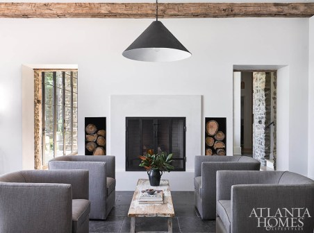 Linen-covered barrel-back chairs surround a streamlined fireplace flanked by steel-lined niches for firewood storage in the kitchen. The concrete chandelier is from Bradley.