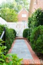Hardscape elements, such as brick and stone, are carefully considered in courtyard gardens where boxwood hedges and other plantings frame the borders.