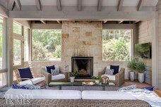 The screened porch was cleverly designed for use in all seasons. The fireplace takes center stage in the winter, while in warmer months, the furniture is flipped to enjoy views of the lake and its lush surroundings.