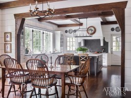 """Open to the dining area and family room, the spacious, light-filled kitchen features a Calacatta island and graphite countertops. The dining table and chairs are both antique and the chandelier is through Circa Lighting. """"Norman and I just had a great time configuring that kitchen and making it a real, workable kitchen,"""" says Bozeman."""