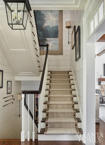 The front stairway creates a warm welcome in this sprawling farmhouse.