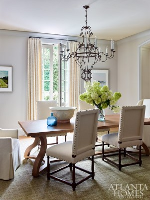 A sculptural iron chandelier from Formations through Jerry Pair adds an ornate touch to the formal dining room, where Alpaca-covered chairs surround a table by Liaigre. The antique rug is from Sullivan Fine Rugs.