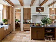 Recessed into the plaster range, a carved wooden panel from A. Tyner Antiques adds a bespoke quality to the kitchen, which is outfitted with white oak cabinetry from Morgan Creek Cabinets, soapstone countertops from Walker Zanger and limestone tile flooring by Paris Ceramics.