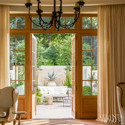 Framed by flowing drapery, the living room's French doors open to a beautifully landscaped courtyard with an outdoor living area.