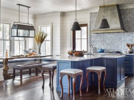 """The wife """"had always wanted a blue kitchen,"""" says Wilkins, who centered her design scheme around a blue Walker Zanger tile backsplash, painting the cabinetry a complementary deep cyan (Sherwin-Williams Anchors Aweigh). The light fixtures are through Hudson Valley Lighting and the barstools are through Century Furniture."""