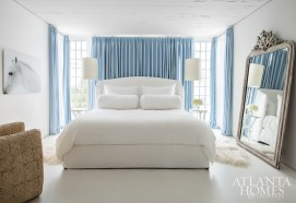 Blue draperies by C&C Milano pay homage to the sun and surf while establishing a unique identity for a stylish guest suite furnished with a bed from Cisco Home and a chair from Mast Alys Beach.