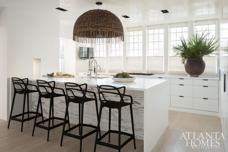 When the contractors dropped the veiny Calacatta marble intended for the kitchen countertops, the homeowners opted to pair the intact piece with white Corian counters. The wicker pendant is by Gervasoni.