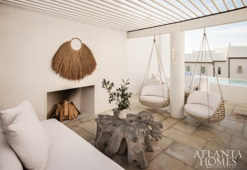 A favorite spot of the owners, the swanky rooftop entertainment area includes a pair of hanging chairs by Dedon and a daybed by Lee Industries around a woodburning fireplace.