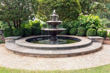 Mature boxwoods and hydrangeas surround the fountain.