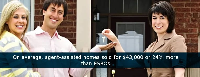 Real Estate Agent handing new homeowners their keys to their new house