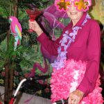 Senior woman toasts the parrot in the palm trees.