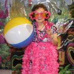 Senior with silly sunglasses, umbrella and beach ball at pool party resident event.