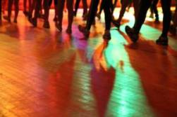 view of set dancing class taking from floor level only showing the legs of the participants