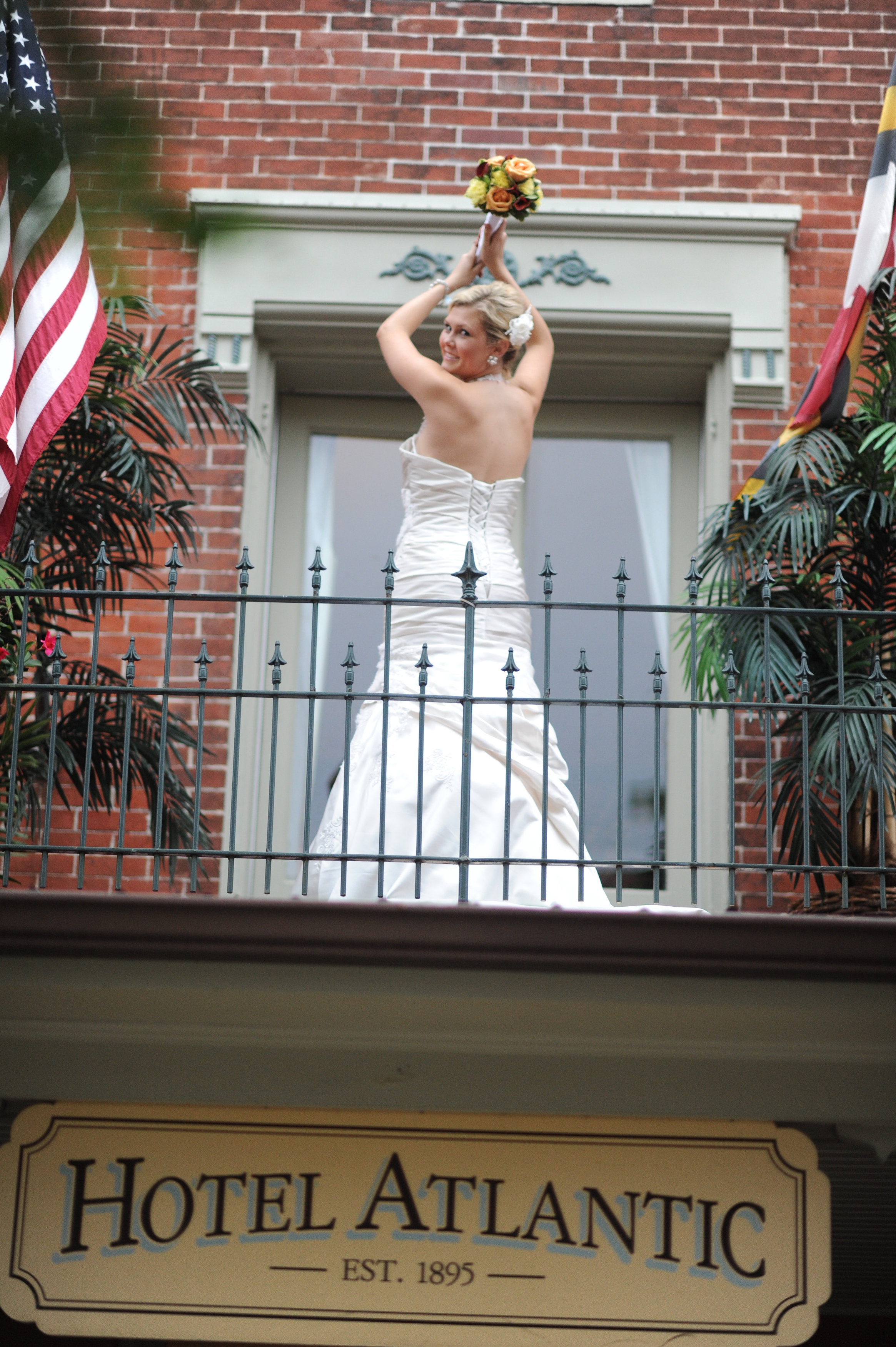 Weddings Main   The Atlantic Hotel   Historic Berlin MD Bride standing on porch of Atlantic Hotel holding bouquet in Berlin MD