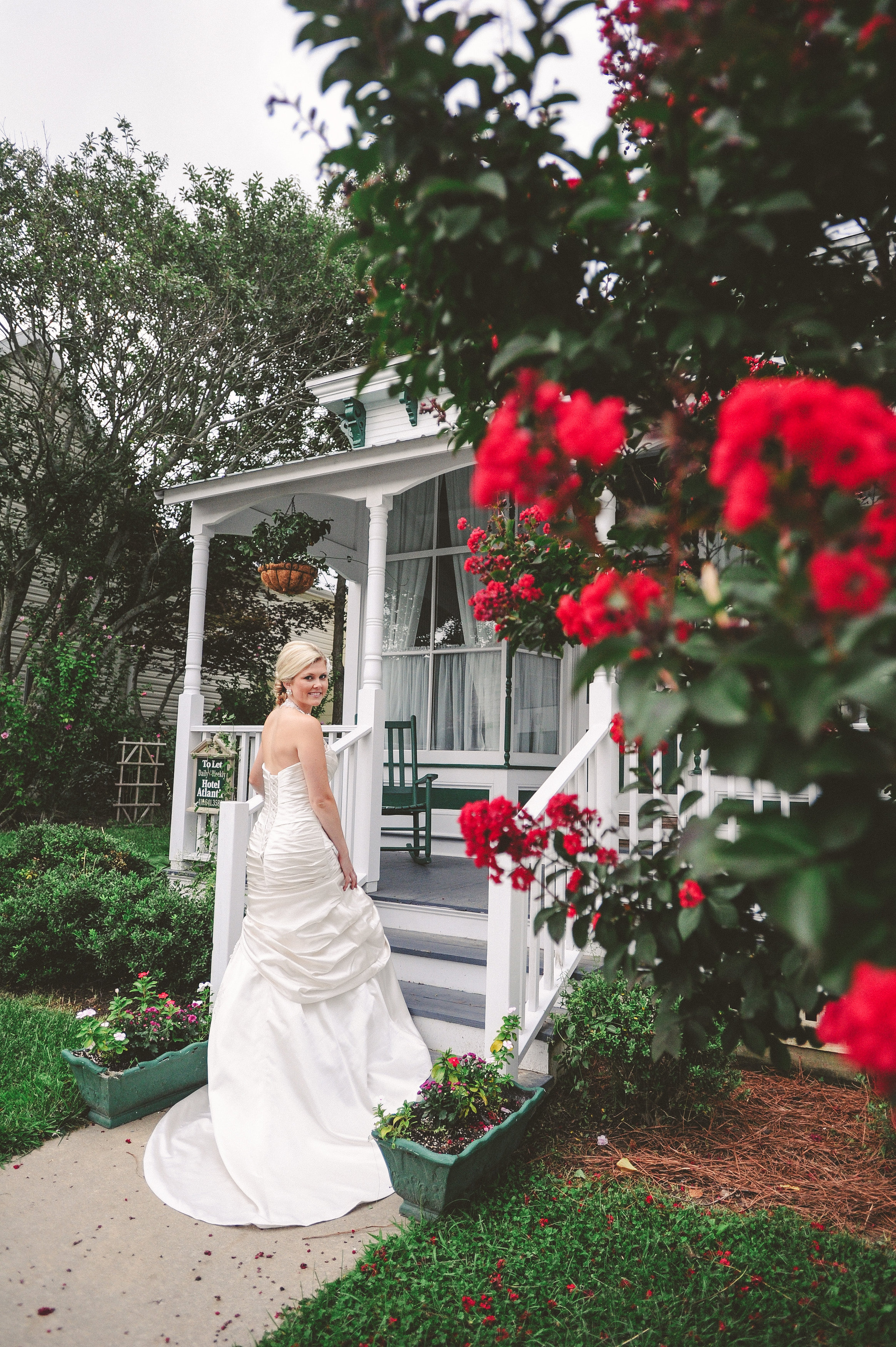 Weddings Main   The Atlantic Hotel   Historic Berlin MD Bride standing back to front porch with red flowers Berlin MD Bustle Gown