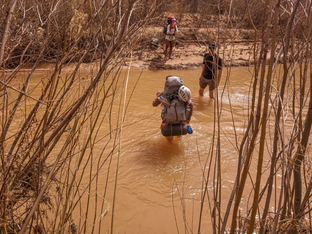 Backpackers crossing river in the desert