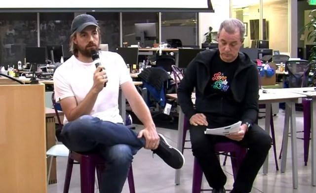 Photo of Atlassian co-CEO Mike Cannon-Brookes and Atlassian CFO James Beer at an all-staff meeting reading questions from staff.