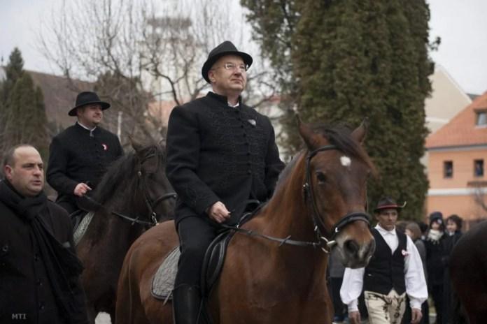 Semjén Zsolt huszár-hagyományőrzőkkel vonul be Kézdivásárhely főterére 2013 március 15.-én. A háttérben Olosz Gergely képviselő látható. Fotó: MTI
