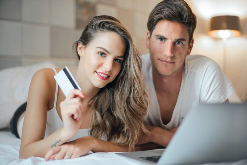 Happy young couple doing purchase on internet together