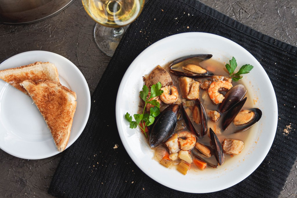 Elegant seafood stew with a cold glass of white wine