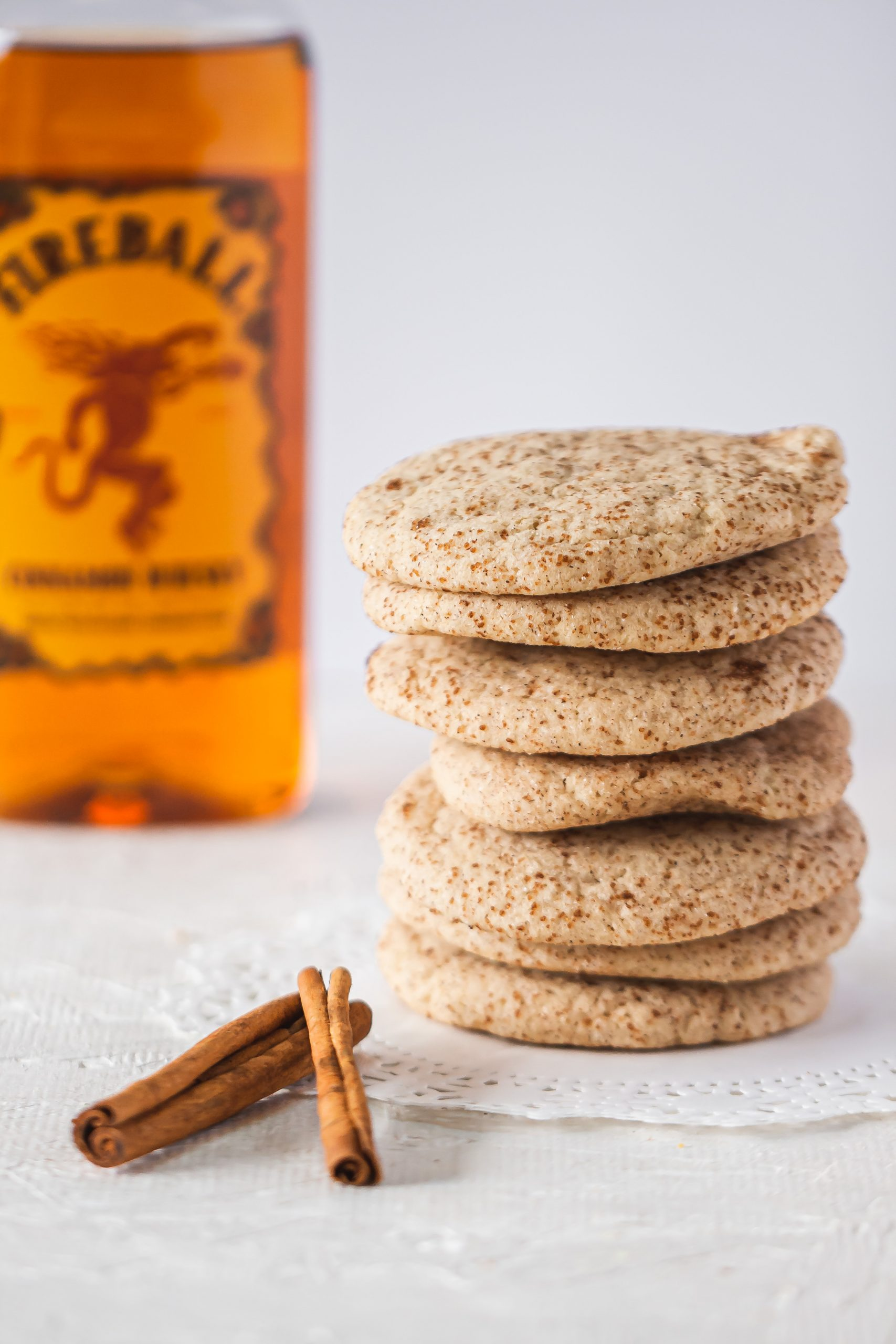 Food photo of stacked snickerdoodle cookies with cinnamon sticks and Fireball