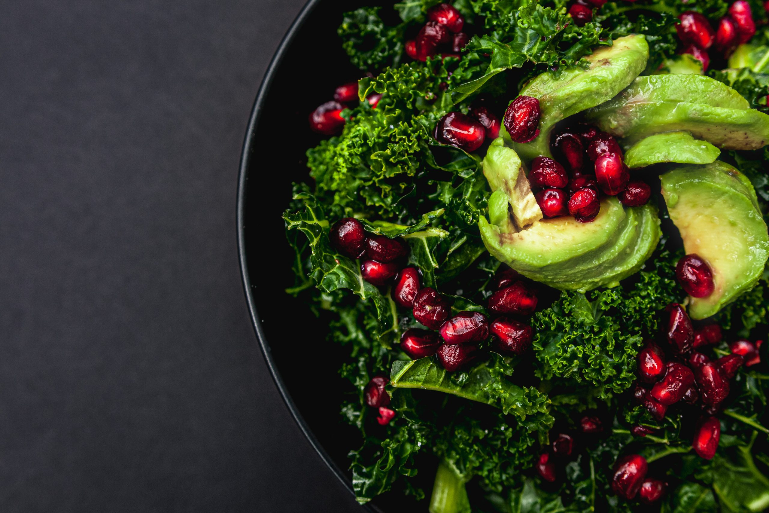 Food photo of kale salad topped with pomegranate and avocado