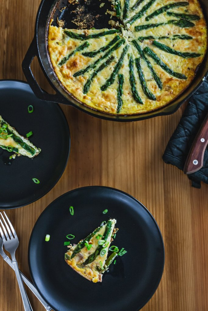 Food photo of asparagus onion and ham frittata in cast iron skillet with plates of sliced frittata