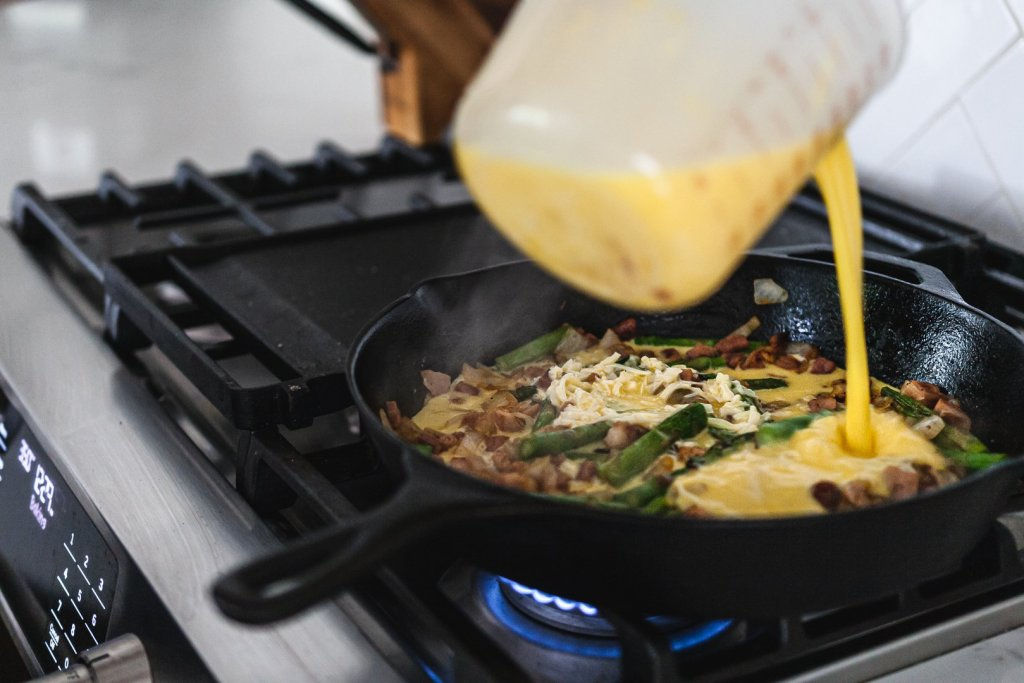 Cooking asparagus onion and ham frittata on stovetop in cast iron skillet.