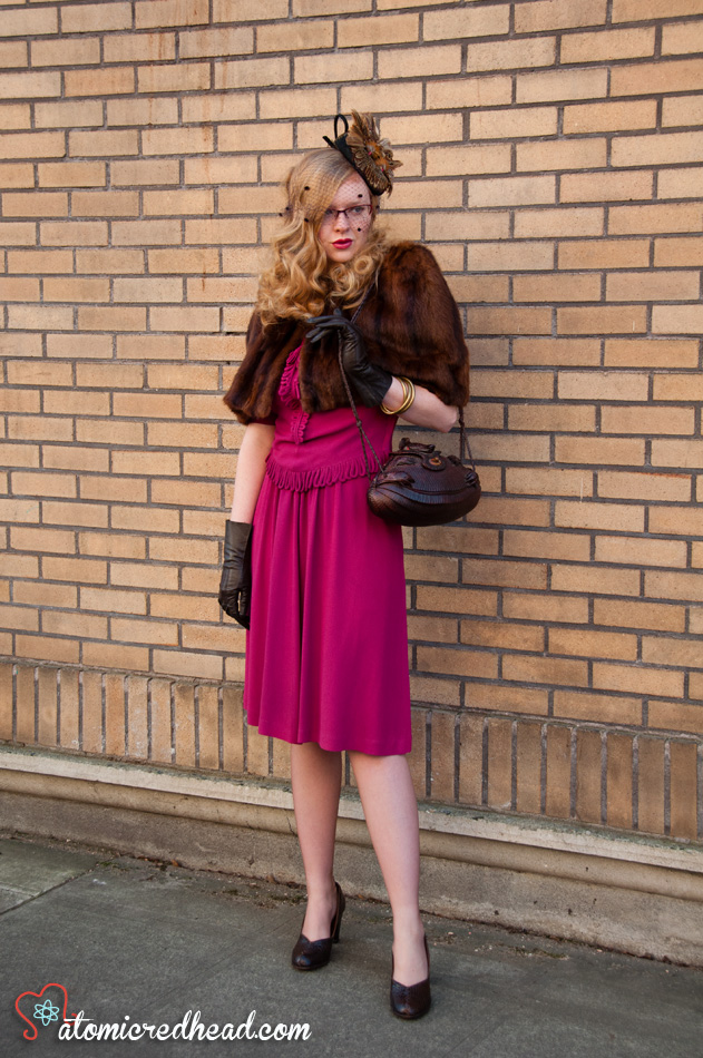 An all vintage ensemble. A hat made to look like it has two birds perched atop, a mink caplet, magenta 40s dress, a purse made out of an armadillo, vintage leather gloves, and alligator shoes.