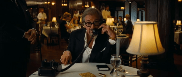 Al Pacino sits at a dining table, talking on a phone.