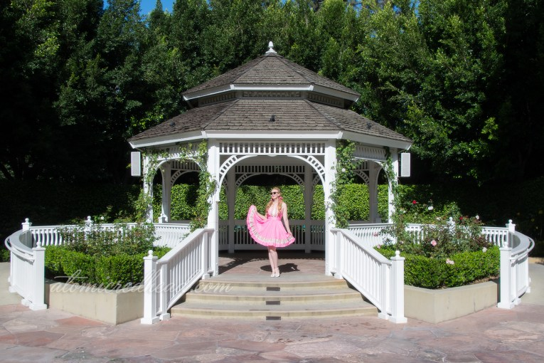 Standing in a gazebo with white roses around.
