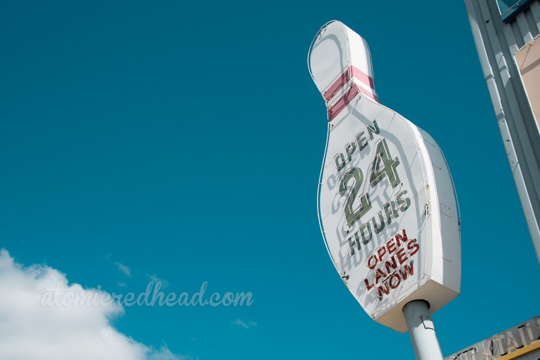 "Close-up of Linbrook Bowl's sign, the bowling pin portion, reading ""Open 24 hours Open Lanes Now"""